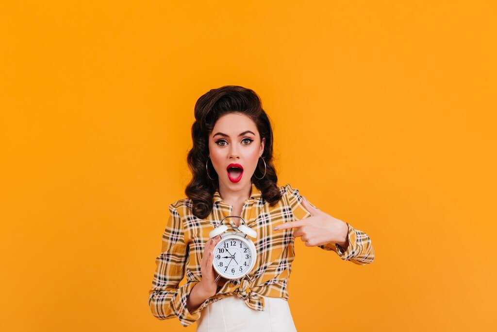 Fashion Photography Trends for 2021 – A must read! fashion photography trends - fashionable brunette lady showing big clock studio shot girl vintage yellow attire - Fashion Photography Trends for 2021 – A must read!
