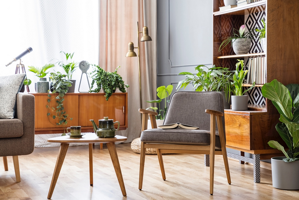 Real photo of an armchair standing next to a small table and a sofa in spacious living room interior with cupboard and shelves with plants behind biophilic design - Natural element in Interior Design Bipophilic Designs - Biophilic Design – A Nature Oriented Interior Design